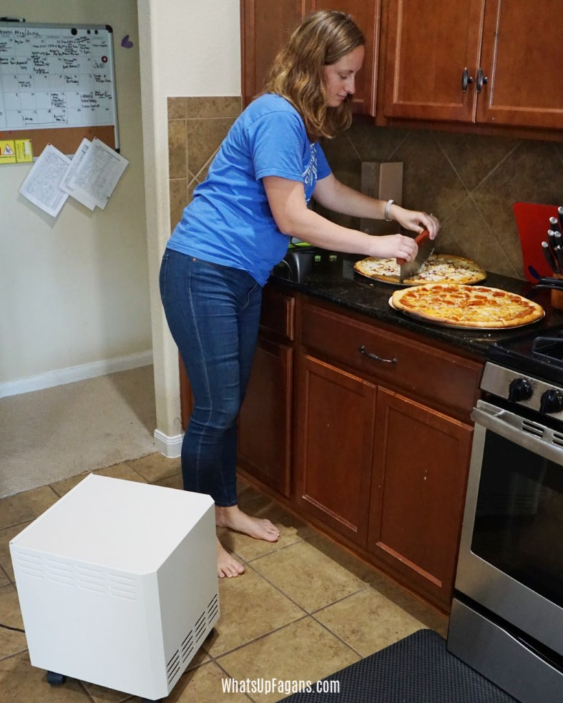 woman cutting pizza that has a strong burn smell in kitchen but is using a cooking odor air purifier called the EnviroKlenz Mobile Air System.