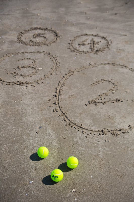 three tennis balls on the sandy beach with four circles with different numbers drawn in them for beach game