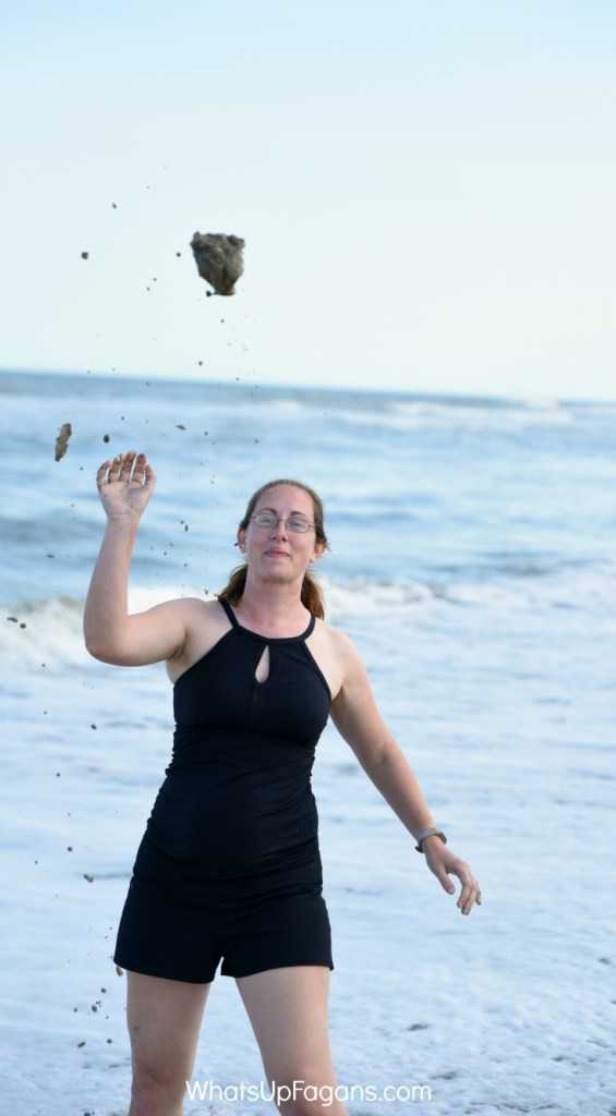 Woman in swimsuit at the beach throwing a sandball as part of beach party games