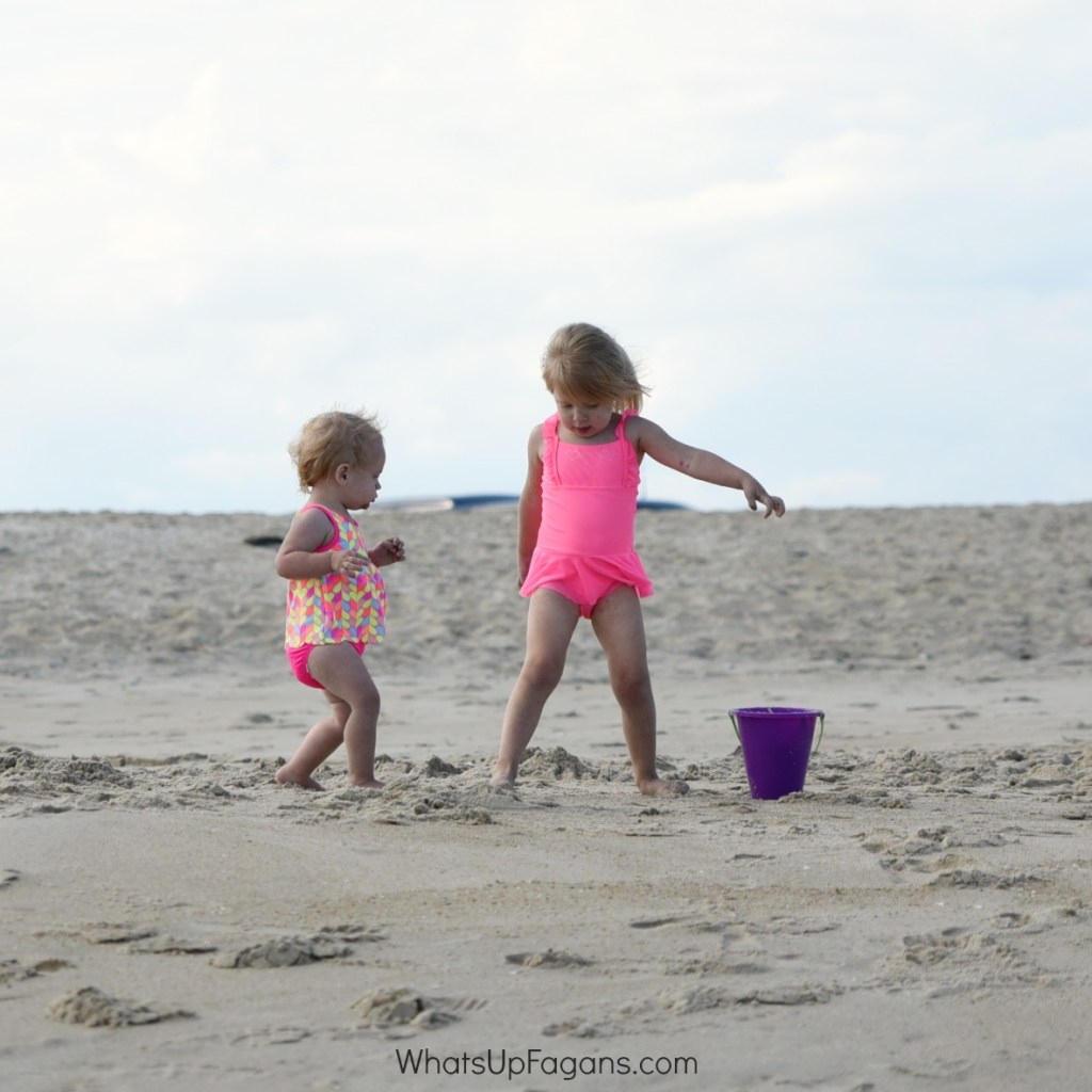 two little girls starting games to play at the beach using buckets and sand