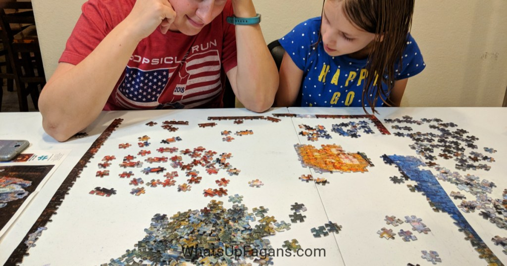 Mom and daughter working on a 1000 piece puzzle as they listen to an audiobook on their Android phone