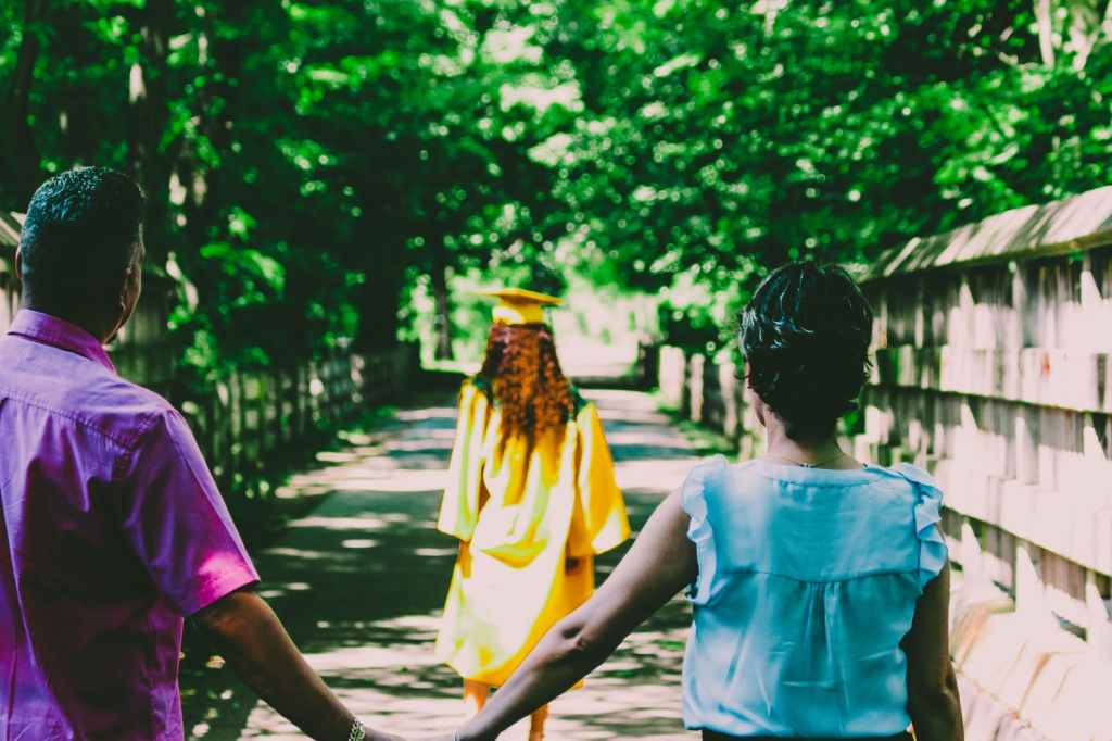 parental involvement in schools can help improve children's outcomes academically, shown by a husband and wife holding hands, looking after their daughter with a yellow graduation gown and cap on.