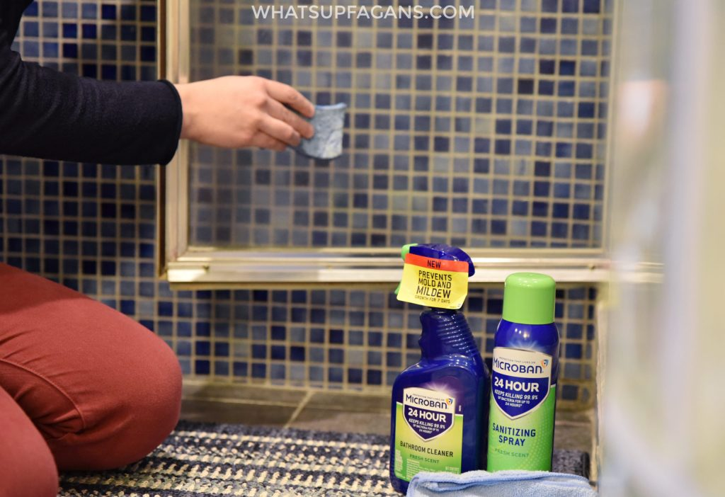 cleaning shower door with MIcroban 24 bathroom cleaner and sanitizing spray so it's both clean and disinfected