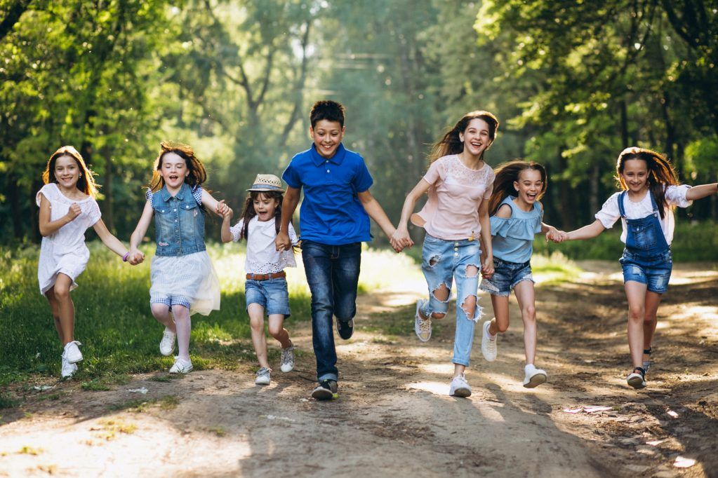 Group of running excited kids holding hands of all ages