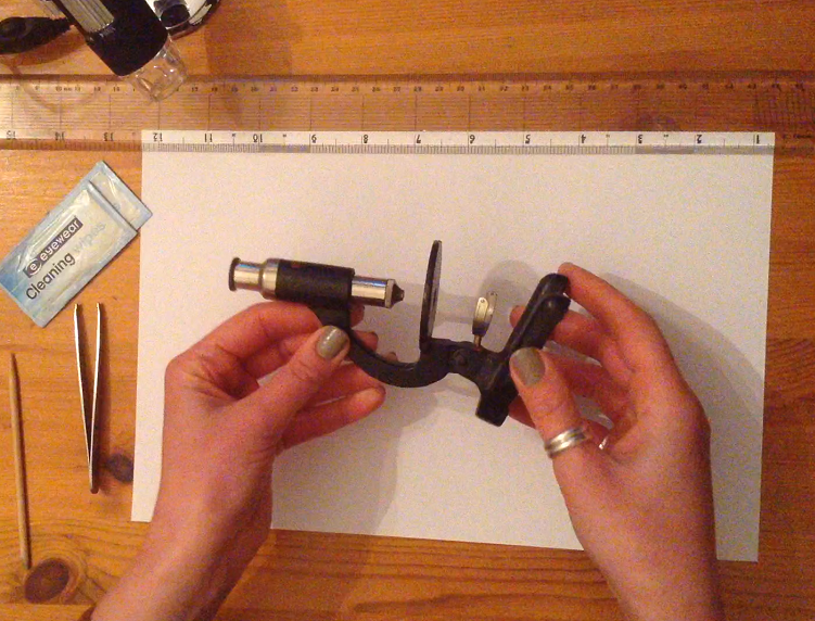 Hands holding toy microscope to inspect the parts