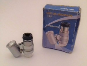 A tiny microscope that consists of two small tubes - one is a light on one side and a lens on the other side.