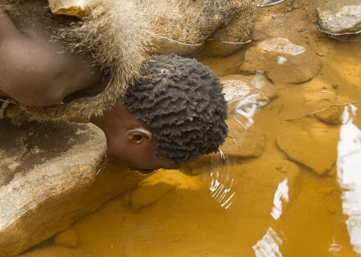 Hadza man drinking water; from IBAH.com