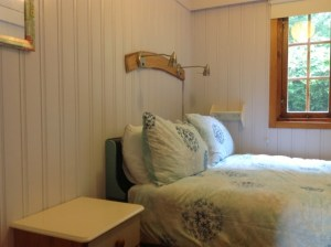 The double bed in quirky Honeysuckle Eco Lodge has a piano lid for a headboard