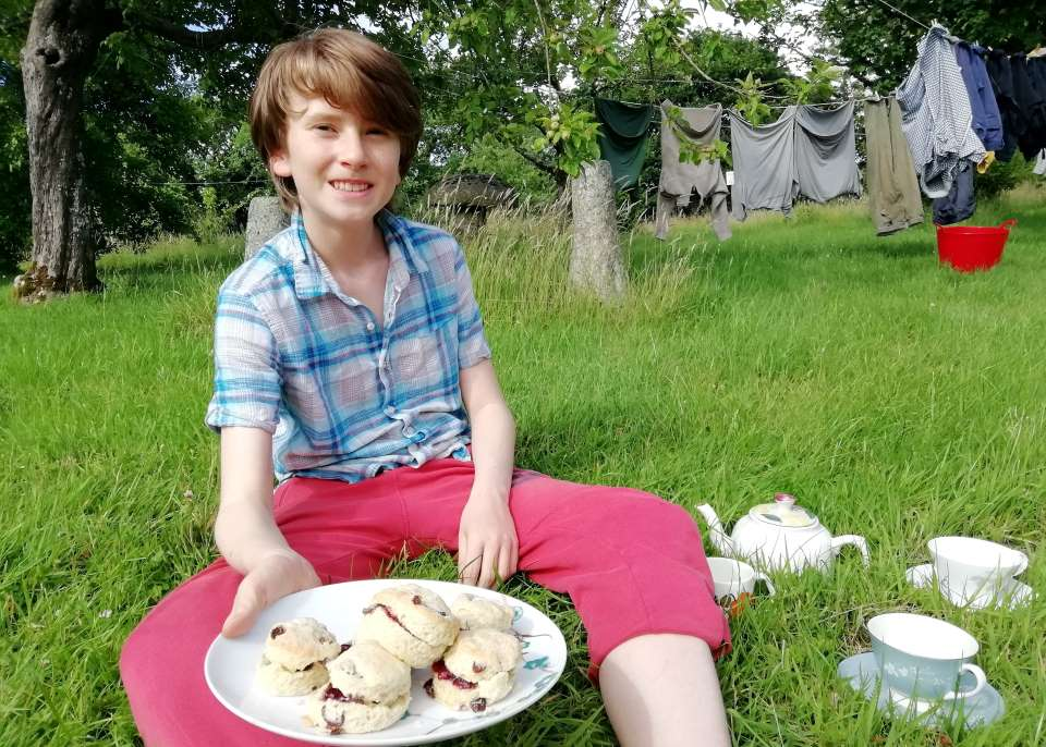 Shows a teenage boy, sat in the orchard at Wheatland Farm, holding out a plate of scones