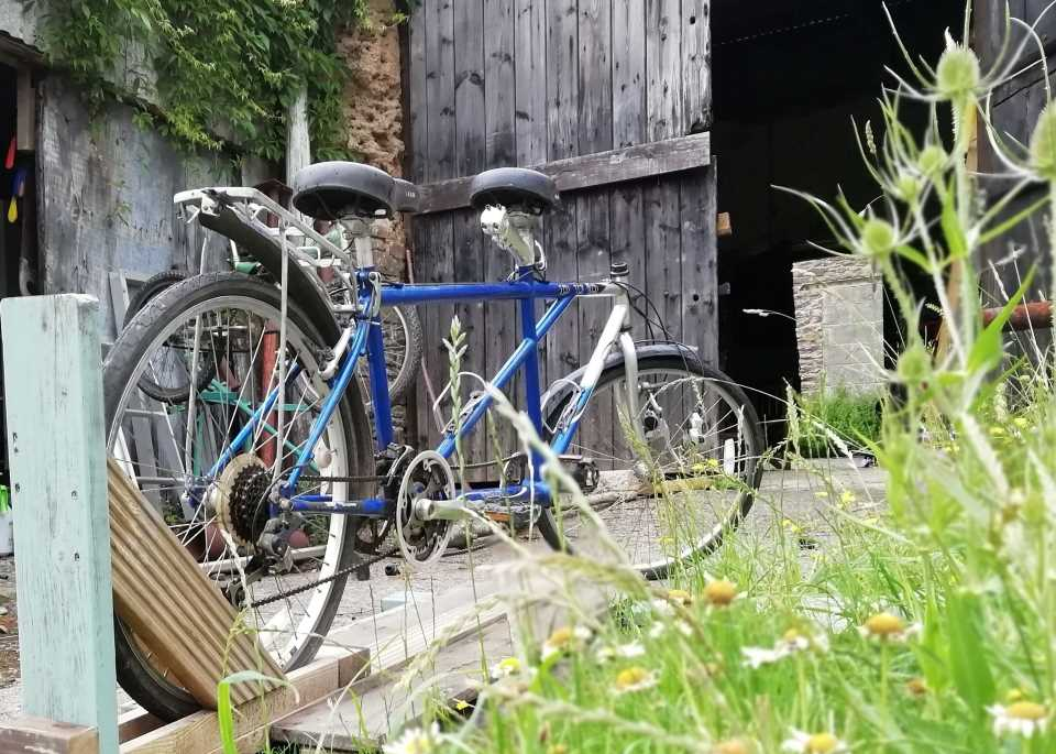 Shows a tandem bike at Wheatland Farm's workshop, undergoing repairs