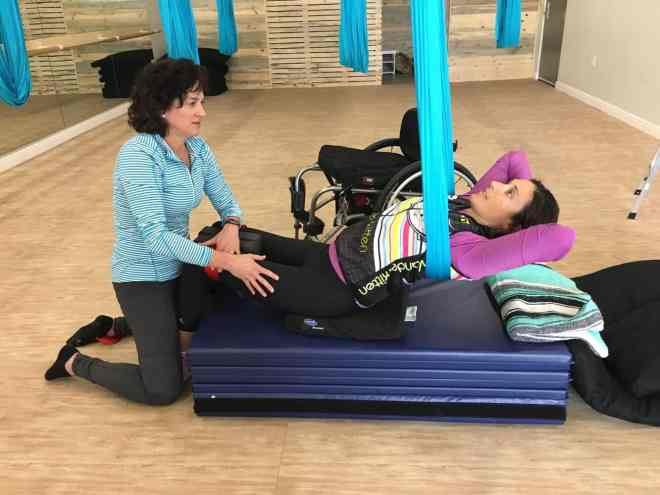 woman and instructor doing adaptive aerial yoga