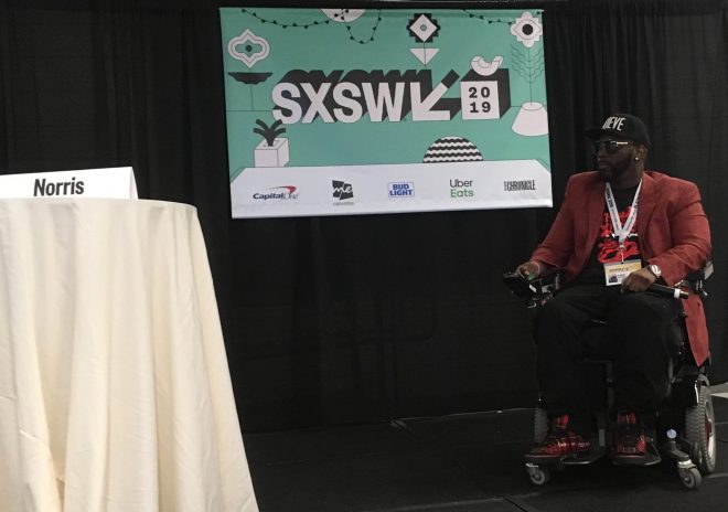Namel Norris presenting on stage with SXSW banner on backdrop