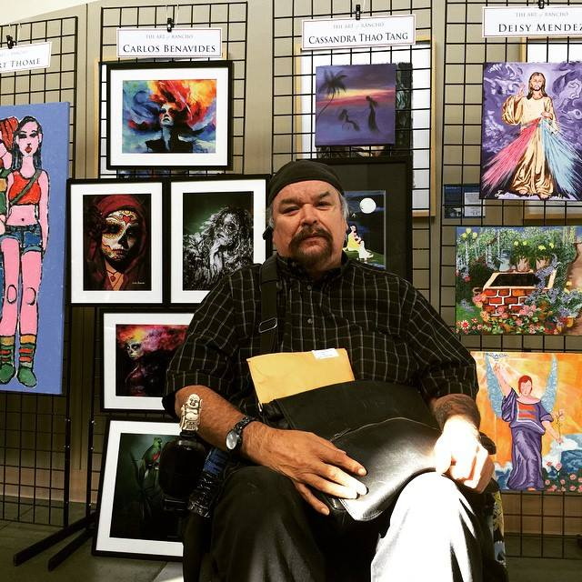 Carlos sitting in front of a wall of his and other people's artwork