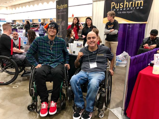 A young main in a wheelchair next to Ray Pizarro in his wheelchair at an expo