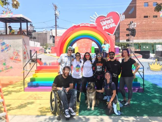 "Group of people, one in wheelchair and one with a service dog, in front of a rainbow display with a ""MAC Loves Pride"" sign."