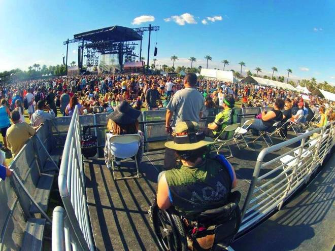 A crowd at an outdoor festival. One man is in a wheelchair in the accessible seating area with an ADA assistant shirt on.