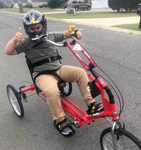 a young boy on a red Freedom Concepts adaptive bike