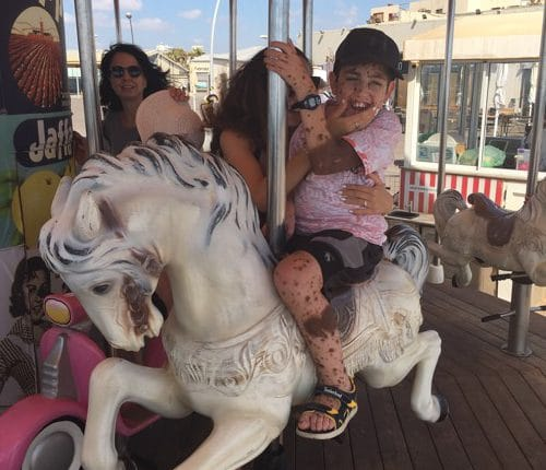Erez rides a merry-go-round with the support of a woman