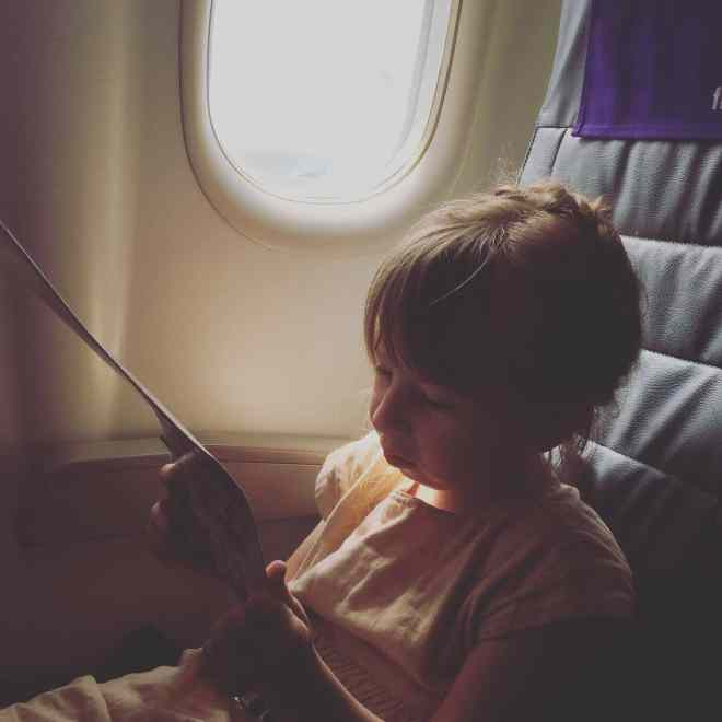 A little girl, Eudora, sits in a window seat on an airplane.