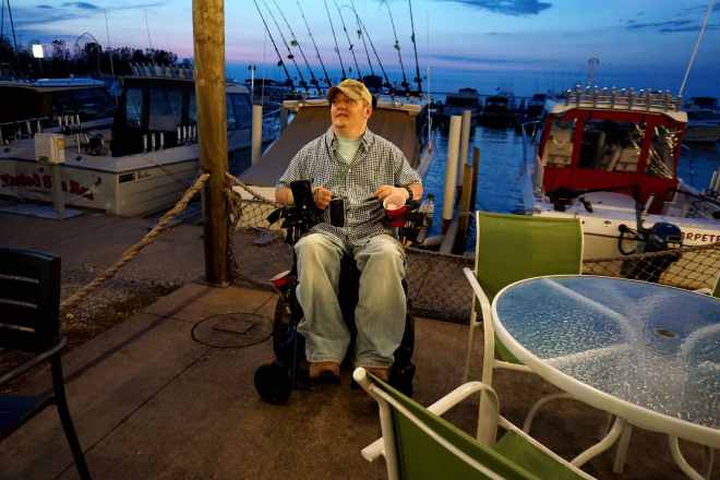 Tim sits in his power wheelchair on a dock. A lake is in the background.