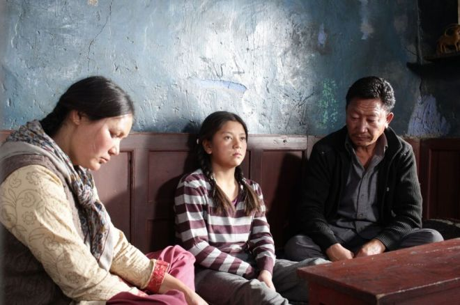 A little girl sits between a man and a woman on a bench.