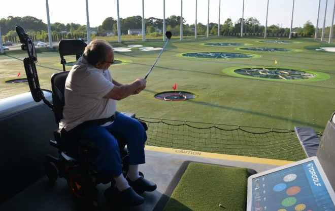 a man in his wheelchair swinging a golf club at a driving range