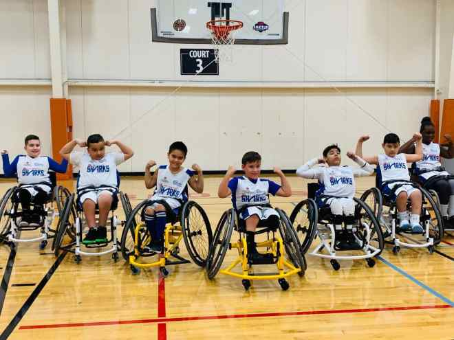 Some of the Fort Lauderdale Juniors wheelchair basketball players flexing their biceps.