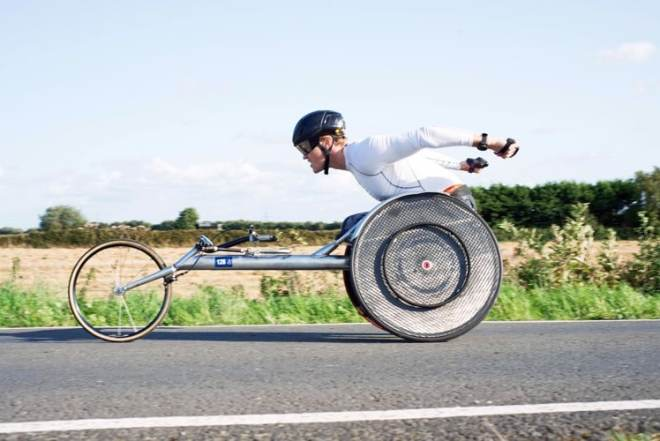 Josh Landmann racing down a street in a racing wheelchair.