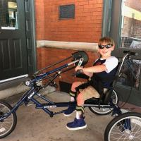 A 9-year-old boy wearing sunglasses on a three-wheeled handcycle