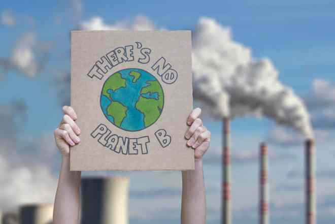 "Two hands hold a cardboard poster that reads, ""There's no Planet B"" with industrial fossil fuel towers spewing smoke in the background."