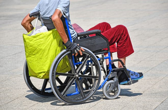 A person in a wheelchair with a reusable shopping bag hooked onto the back.