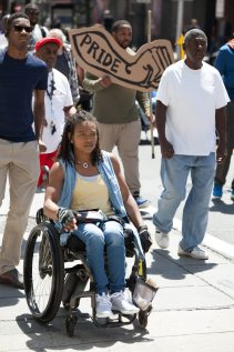 """A woman in a wheelchair at the Disability Pride Philadelphia parade. Several people are marching behind her. One holds a """"Pride"""" sign in the shape of a forearm and fist."""