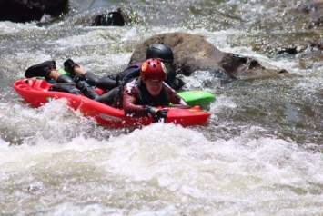 Blakely rides a bellyak down a river with rapids.