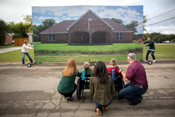 The Copp family and Joanna Gaines crouch down in front of their soon to be revealed new home.