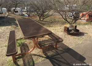 """Typical """"sitting area"""" with picnic table and grill."""