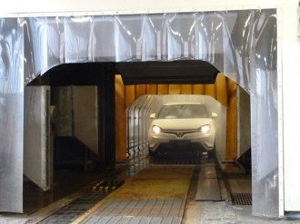 Here a new MG3 is seen as it is about to emerge from the 'Storm Test' chamber, in which each completed car is sprayed with water at high pressure.