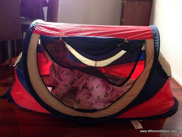 Toddler lying down in travel crib