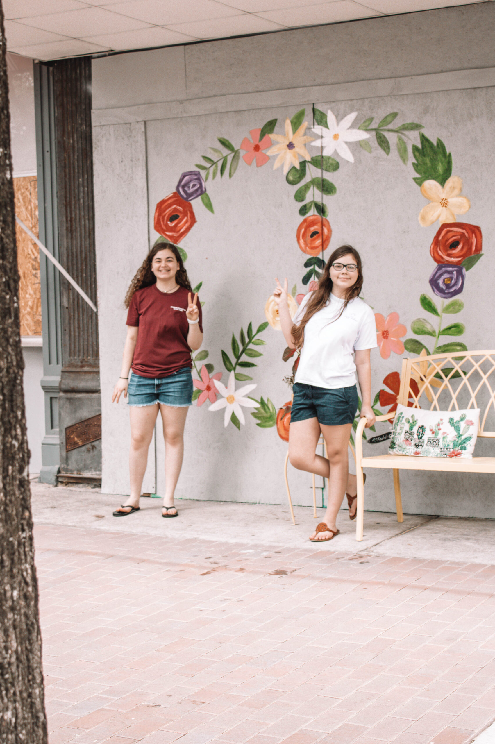 two girls standing in front of a floral peace sign mural