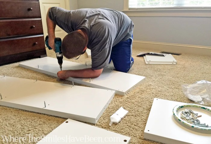 Assembling a white IKEA Kallax shelf unit using a power drill.