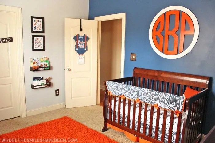 LOVE this giant circle monogram above the crib! It's perfect for a baby boy's room! Take a tour of this Navy & Orange Modern Woodland Nursery! | Where The Smiles Have Been