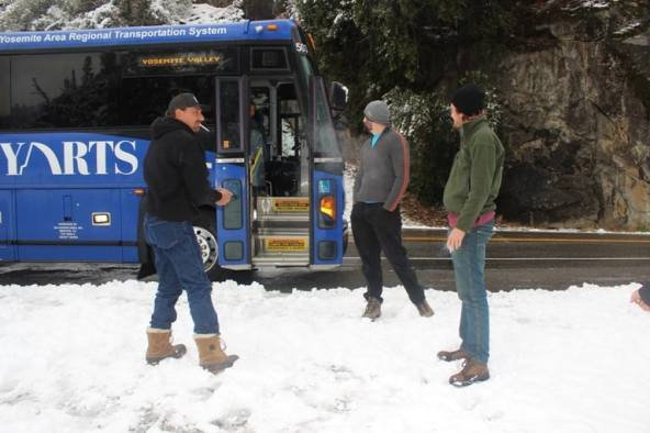 Guys standing in snow by the bus