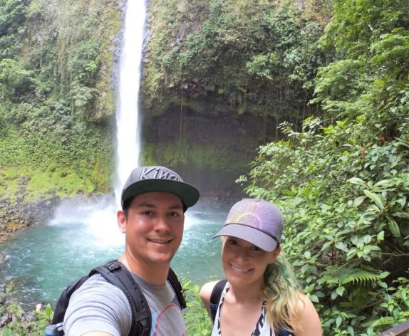 Selfie pic of a couple in front of La Fortuna Waterfall.