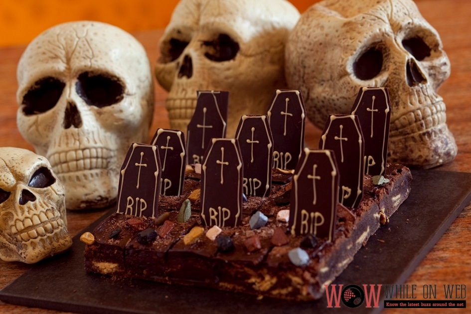 Ghoul's Graveyard Brownies Dark chocolate chips brownies bleeding with chocolate glaze and vanilla shortbread headstones mark on each slice.