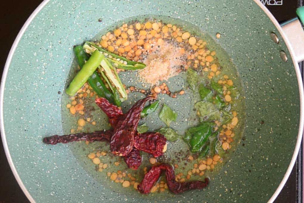 Dry red chillies, green chillies and hing added in the pan