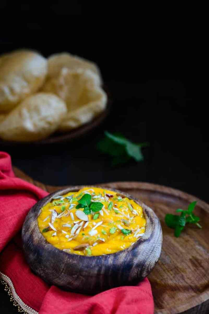 Aamras is a famous Gujarati and Maharashtrian dish made by pureeing ripe mangoes with some sugar, cardamom powder. Aamras and piping hot poories taste heavenly together!
