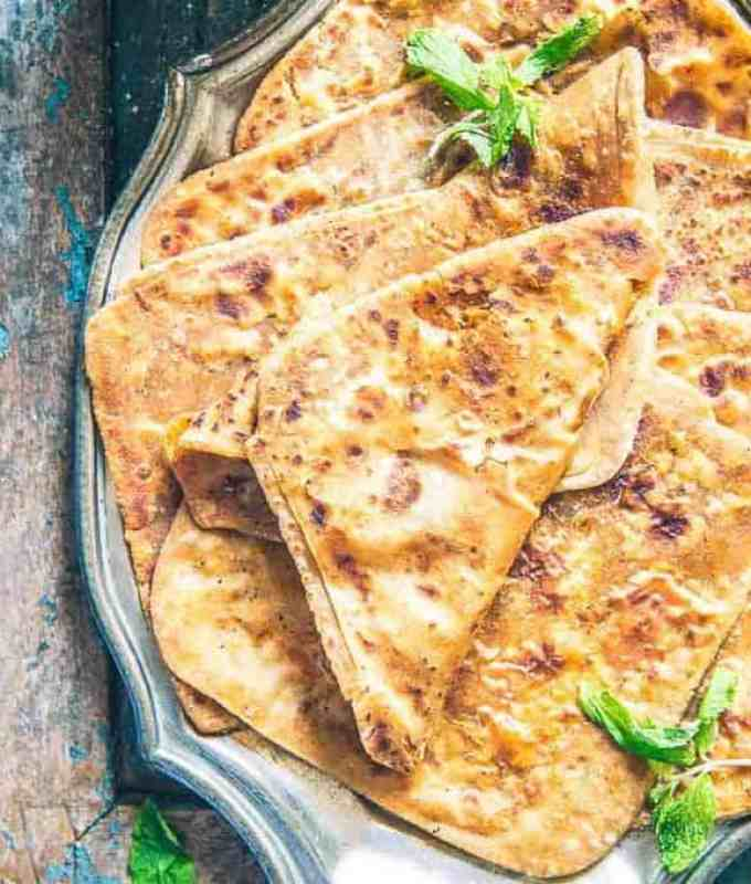 Add whole wheat flour and ghee in a bowl. Mix well using your fingers. Add water and knead a soft dough. Cover the dough and keep aside for 30 minutes. Mix Salt, red chilli powder, amchoor powder, garam masala powder, fennel powder and ajwain in a bowl. Heat a tawa or griddle. Make lemon size balls from the dough. Dust and roll the dough ball to make a 4 inch circle. Apply oil on the circle and sprinkle some of the powdered masala on the circle. Fold the sides to bring them to centre. Apply oil again and then fold the dough to 1/3 rd and then again till the end. Dust and roll again to make a 5 inch square. Transfer the paratha on the hot griddle. Cook until brown spots appear on both the sides. Apply oil and cook again until nicely browned. Keep pressing the paratha with the back of a ladle while cooking. Serve paratha hot with tea or any curry.