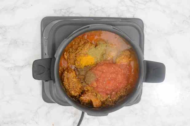 Tomatoes, coriander powder, turmeric powder, garam masala powder and a cup of water added in the pan.