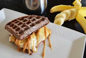 Chocolate Waffle Sandwich with Whipped Cream Bananas and Peanut Butter Drizzle
