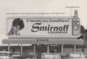 a 1960's billboard with a coy looking woman, a bottle of smirnoff and the words, it takes your breath away