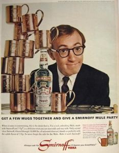 a pront ad from a 196070's magazine showing woody allen next to a tower of moscow mule copper mugs and a smirnoff bottle